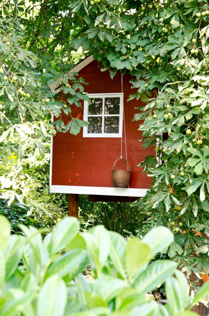 Garten im Sommer und Bilder vom selbst gebauten Baumhaus im Look eines schwedischen Holzhauses
