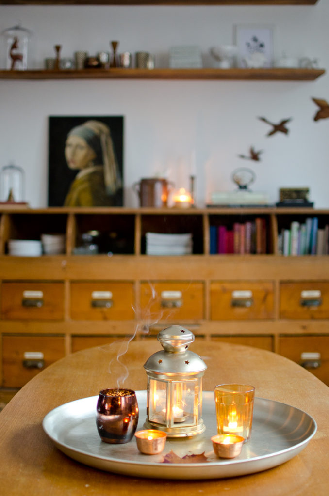 Dekoideen für das Wohnzimmer im November mit vintage Bild und Illex Zweig auf altem Apothekerschrank