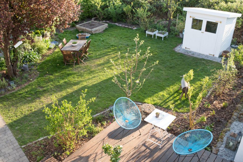 Blick von oben in den Garten mit Holzdeck und Rasen im April