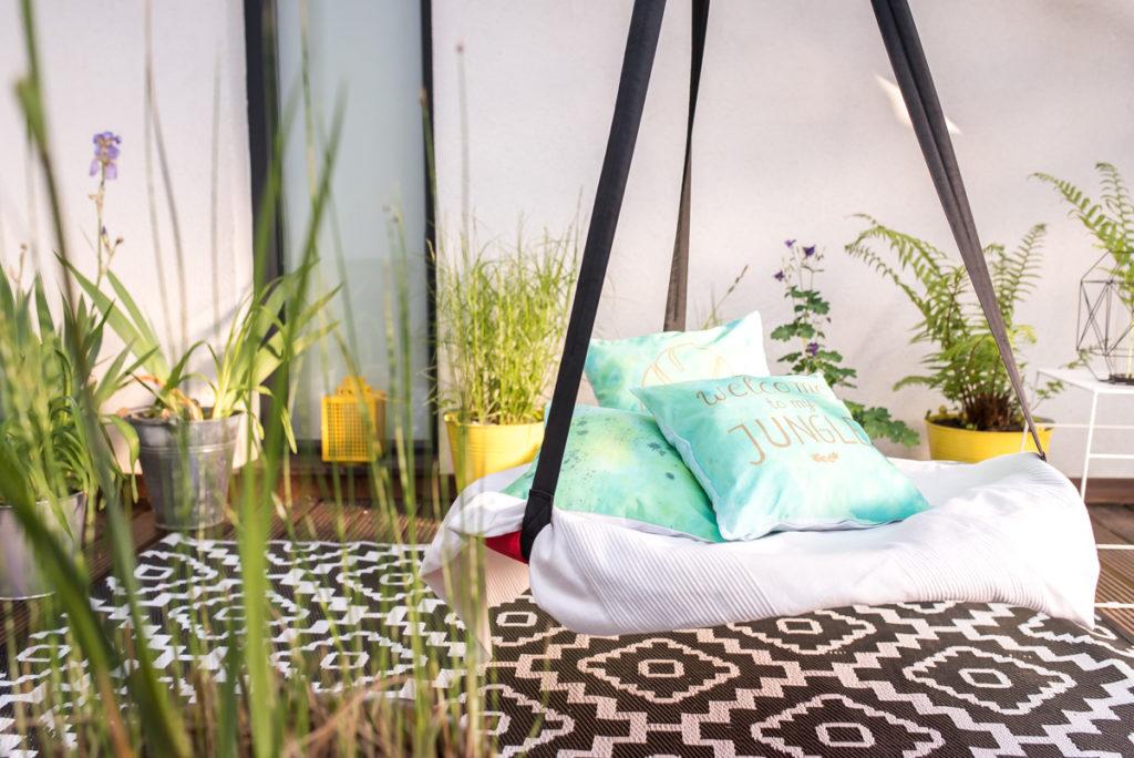 Gemütliche Sitzecke mit Schaukel und Dschungel Pflanzen in Zinkeimern auf dem Holzdeck