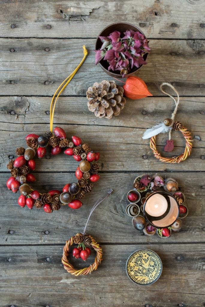Selbst gemachte do it yourself Kränze mit Hagebutten und Tannenzapfen als DIY Deko für das Wohnzimmer im Herbst