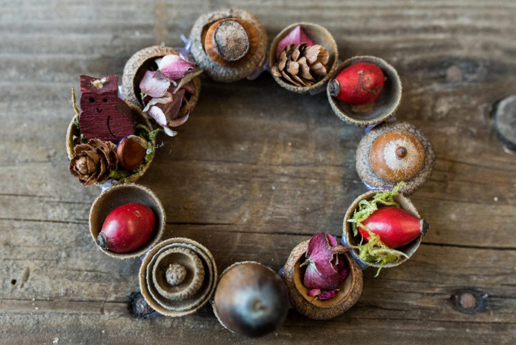 DIY Herbstdeko mit kleinen Kränzen und Anhängern aus Hagebutten, Tannenzapfen und Eicheln als selbst gemachte do it yourself Deko für das Wohnzimmer