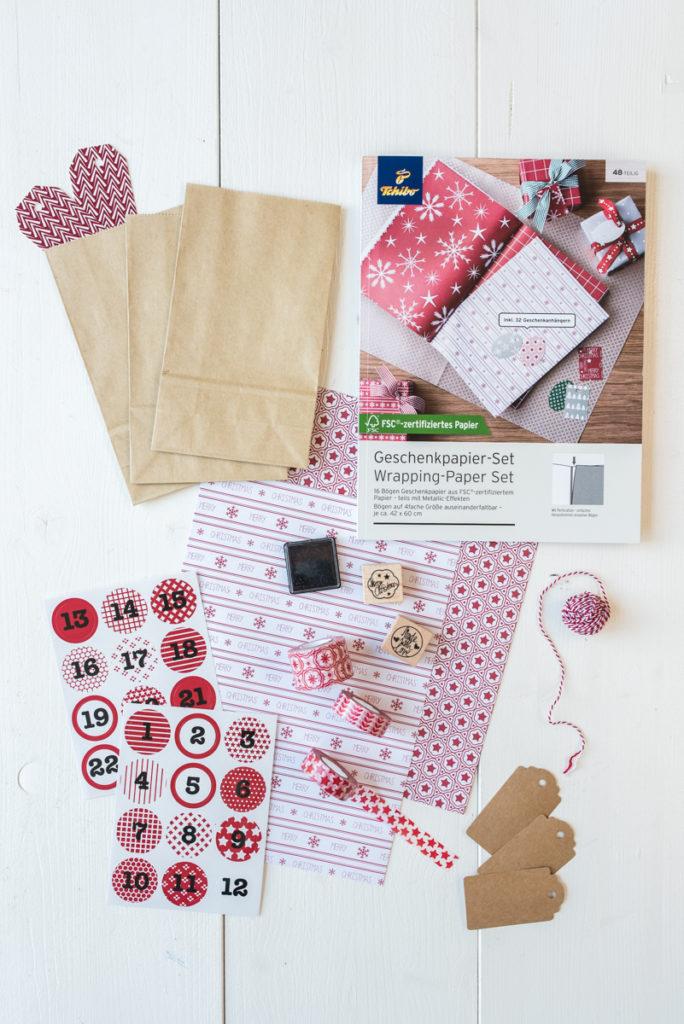 selbst gemachter DIY Adventskalender in einer Holzkiste mit Tüten, Washi Tape und Bändern von Tschibo in Naturtönen und Rot