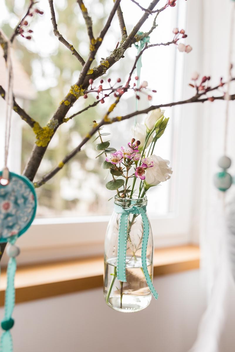 Natürliche Osterdeko mit Eiern in Pastellfarben und kleinen Hängevasen am Pflaumen Zweig