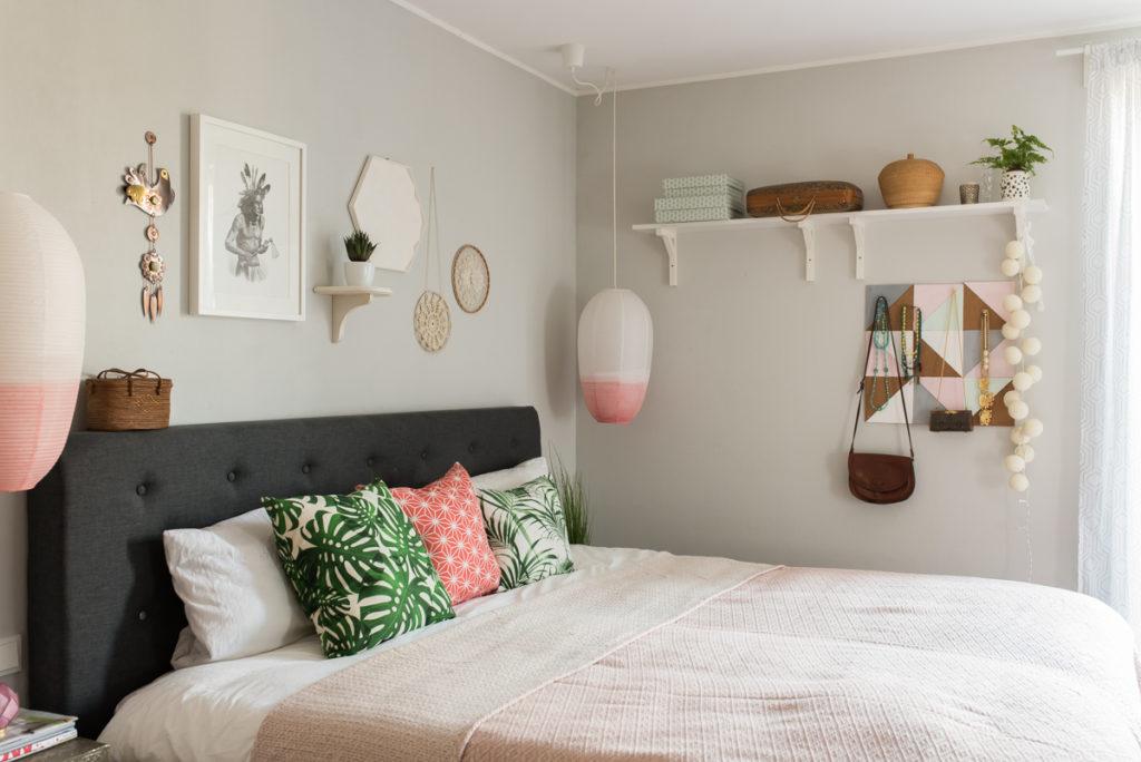 Dekoideen für das Schlafzimmer im skandinavischen vintage Look mit grauem Boxspringbett, grauen Wänden und Deko in der Farbe Koralle und Mint