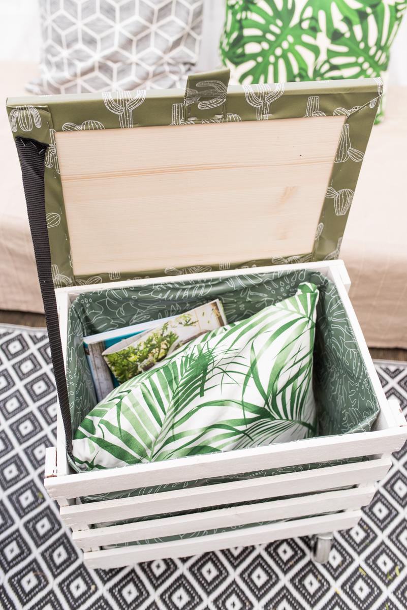Anleitung für einen upcycling DIY Balkontisch auf Rollen aus einer Obstkiste mit Deckel zur Aufbewahrung von Kissen für den Balkon