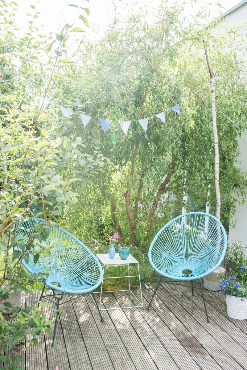 Deko im Garten mit Acapulco Chairs, Wimpelgirlande und kleiner Sitzecke im Grünen