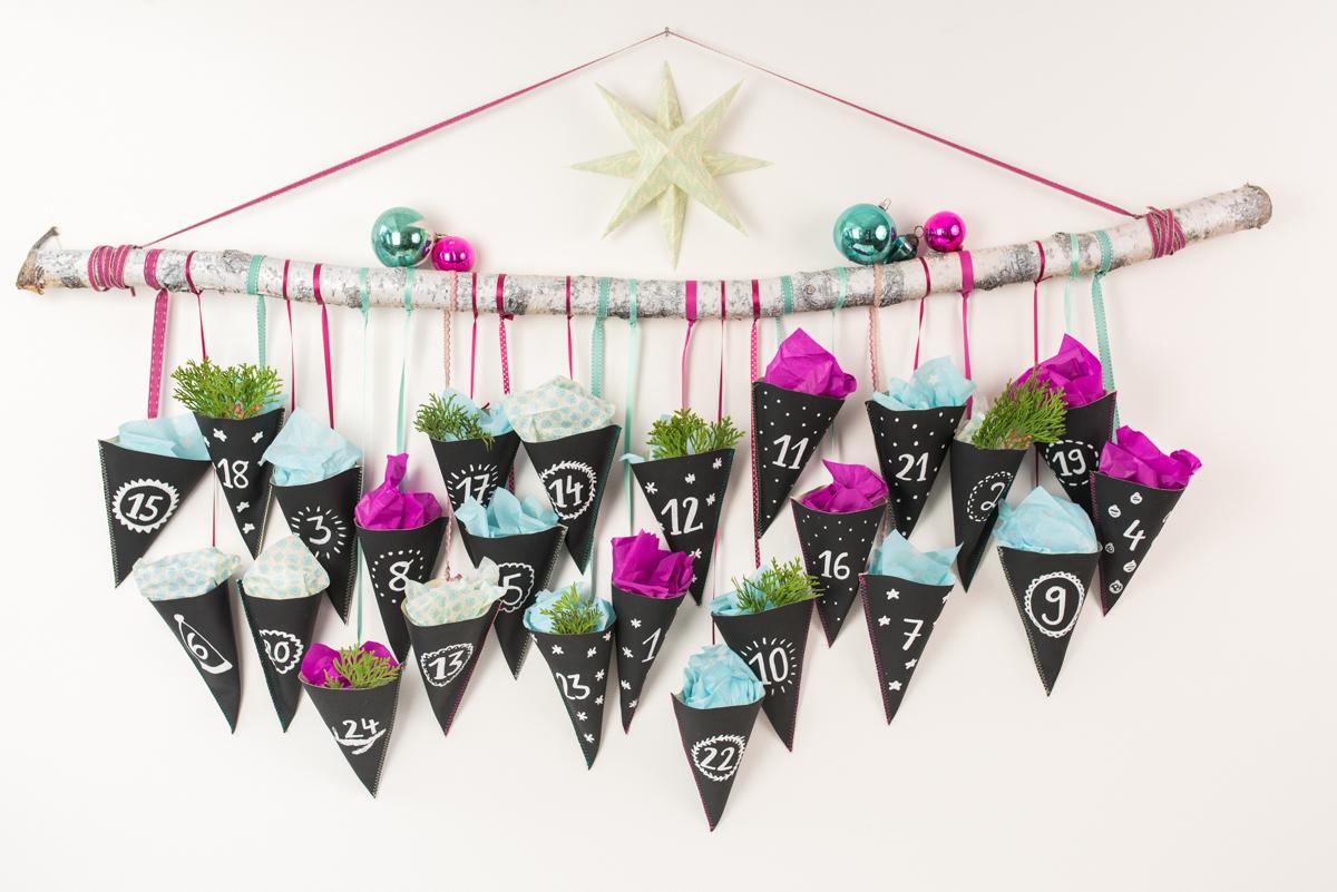 Anleitung für einen selbst gemachten DIY Adventskalender an einem Ast mit Spitztüten aus schwarzem Tafelstoff und Deko in Pink und Türkis als Weihnachtsdeko im Advent