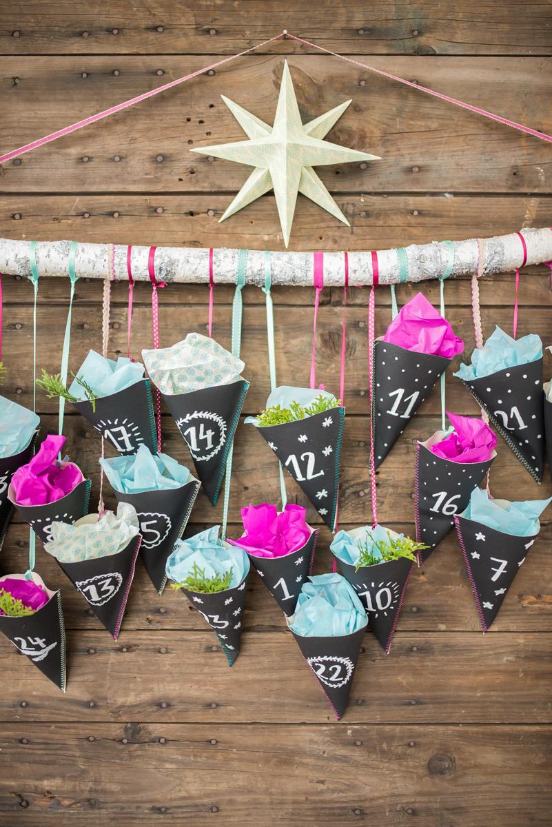 Anleitung für einen selbst gemachten DIY Adventskalender aus schwarzem Tafelstoff mit Pink und Türkis mit Spitztüten an einem Ast als Weihnachtsdeko