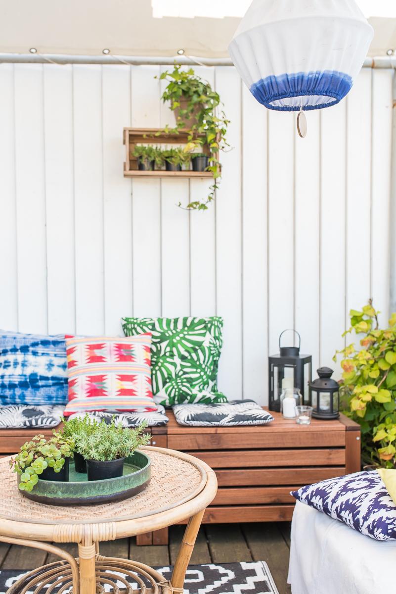 So richtet ihr euch ein outdoor Wohnzimmer auf dem Balkon im Boho Look ein und dekoriert mit bunten Kissen, Teppichen und Pflanzen in Kübeln