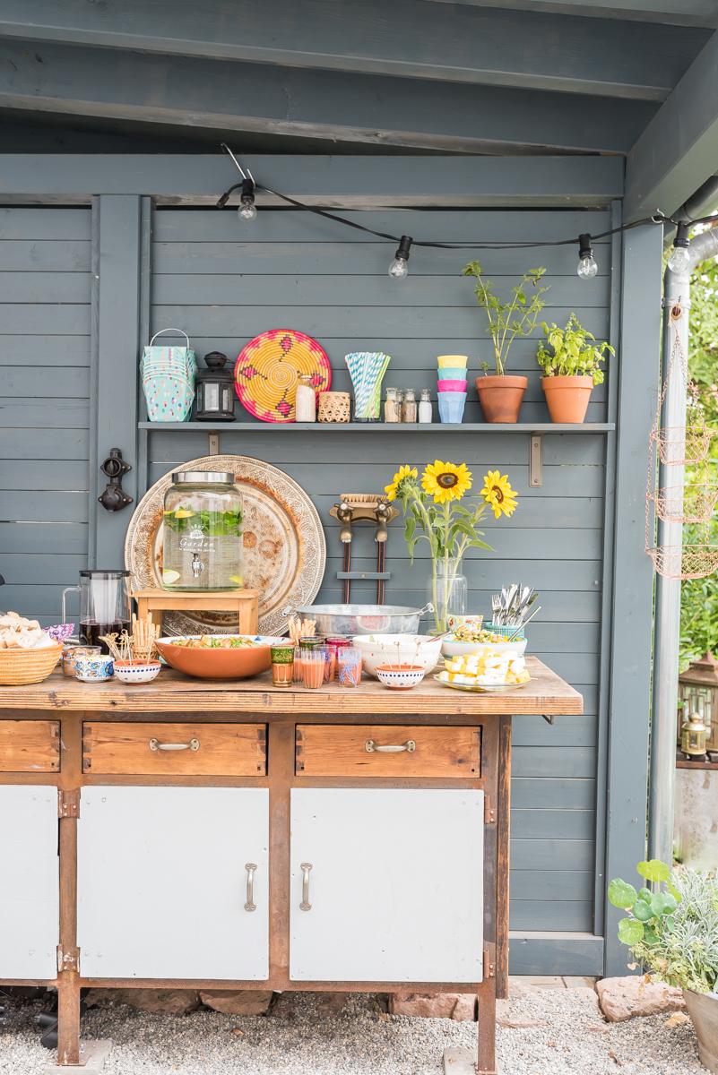 Dekoideen für die Gartenparty im Sommer mit bunten Lampions und Blumen und Leckereien vom Grillbüfett