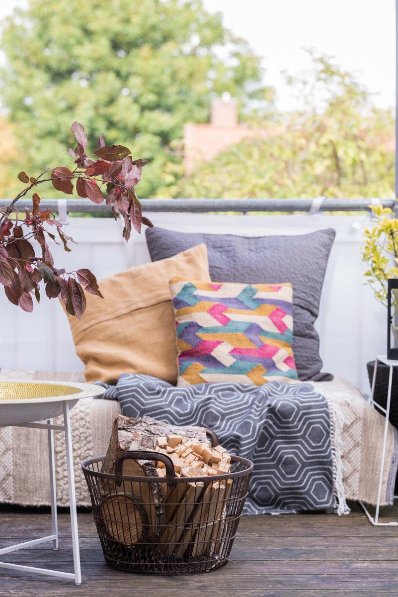 Dekoideen für Herbstdeko auf dem Balkon mit Windlichtern, Lichterketten und gemütlichen Kissen im Boho vintage Look