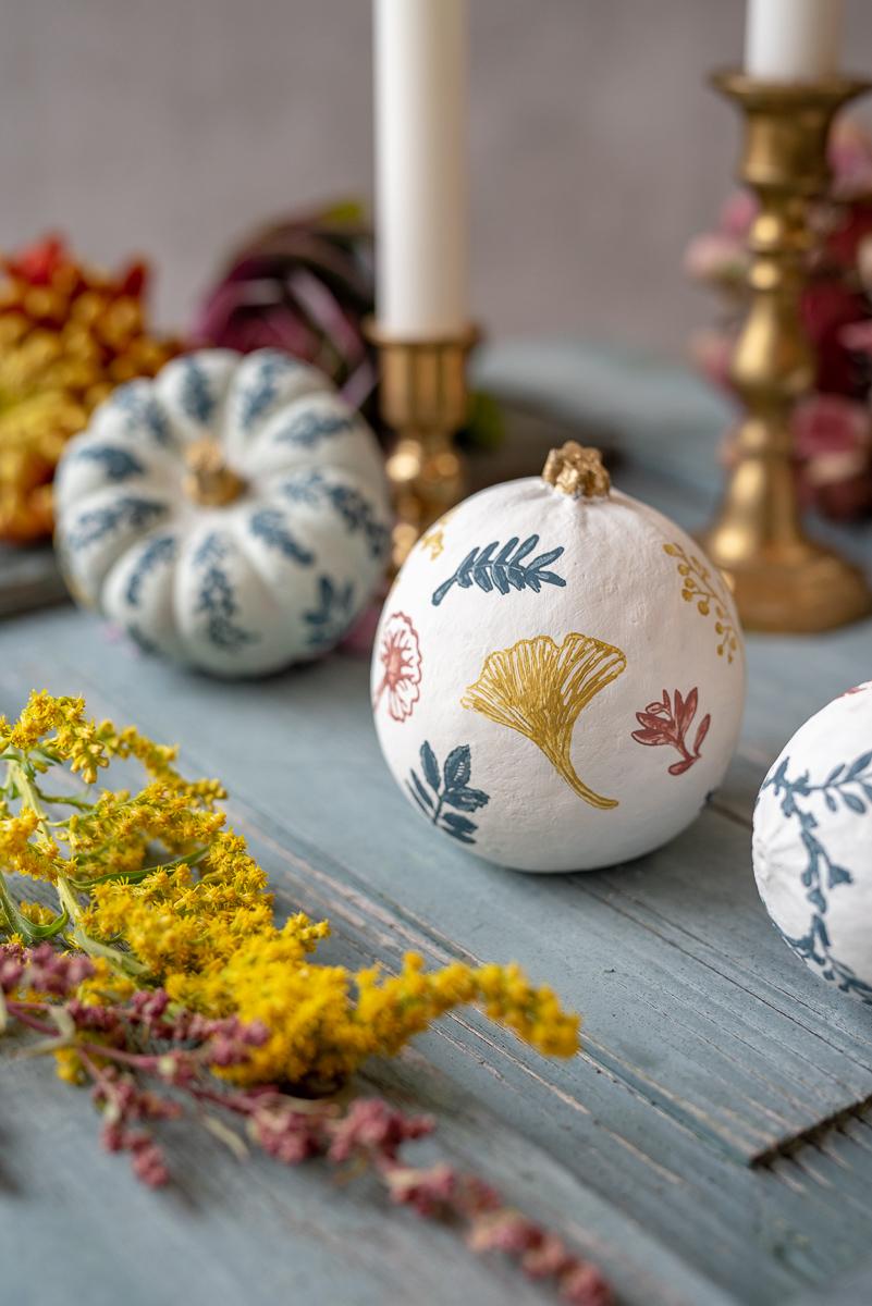 Anleitung für bemalte und mit Stempeln verzierte Kürbisse im vintage Look in Rosa, Senfgelb und Petrol als Herbstdeko für den Tisch