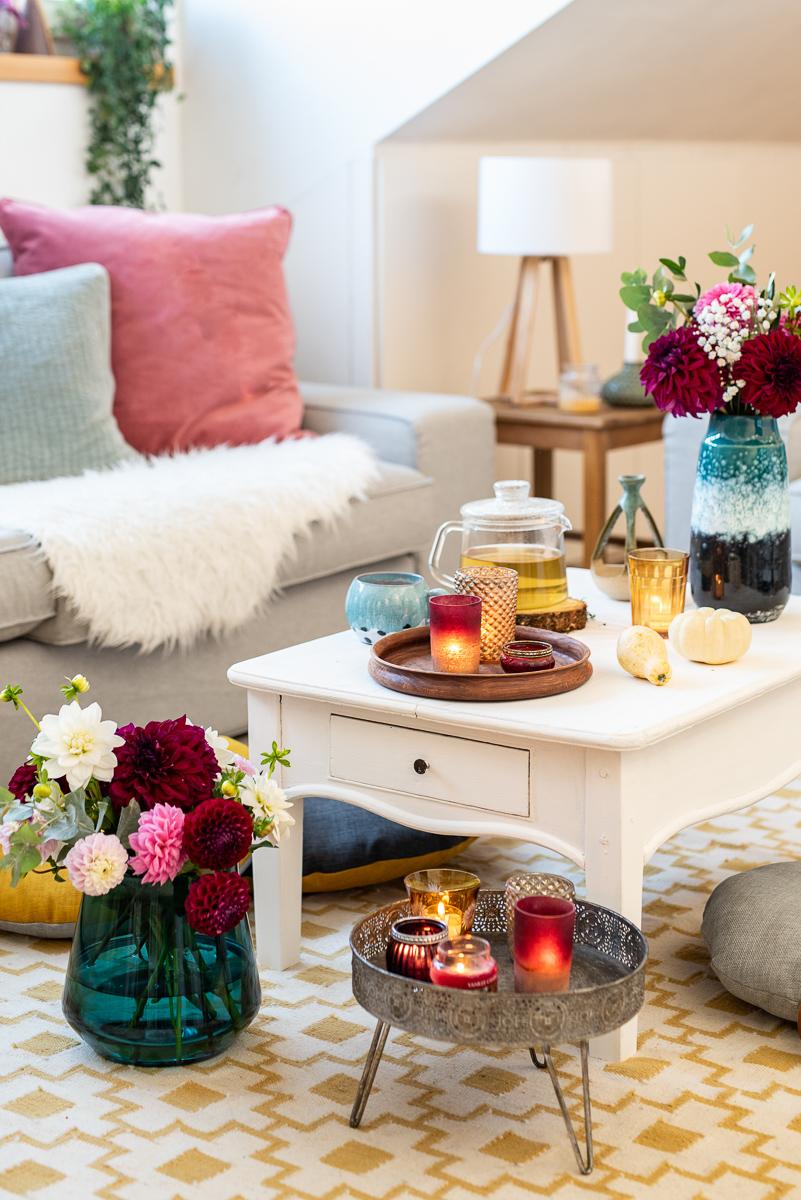 herbstliche Dekoideen für das Wohnzimmer im Herbst mit Kissen in bunten Farben aus Samt, gemütliche Decken für das Sofa, Kerzen und Blumendeko mit Dahlien