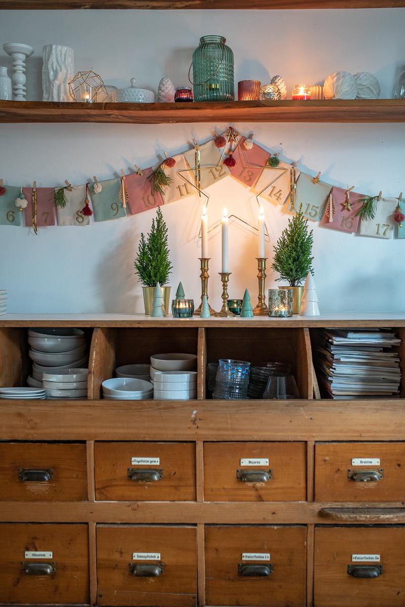 Anleitung und Inspiration für einen selbst genähten und wieder verwendbaren DIY Girlande Adventskalender aus Stoff in Pastellfarben mit Gold und Pompoms aus Wolle