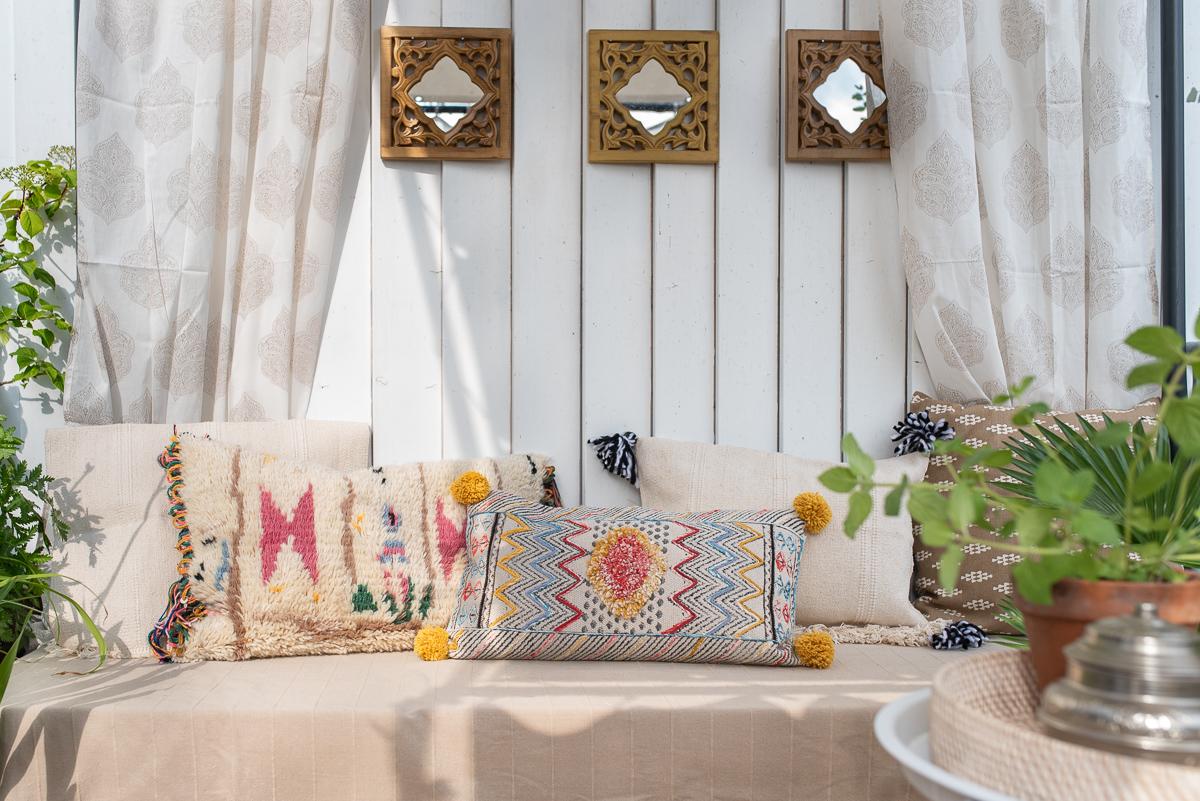 Dekoideen für den Balkon im Sommer im Boho Ethno Look mit Kelim Kissen, Jute Teppich und Pflanzen im orientalischen Stil