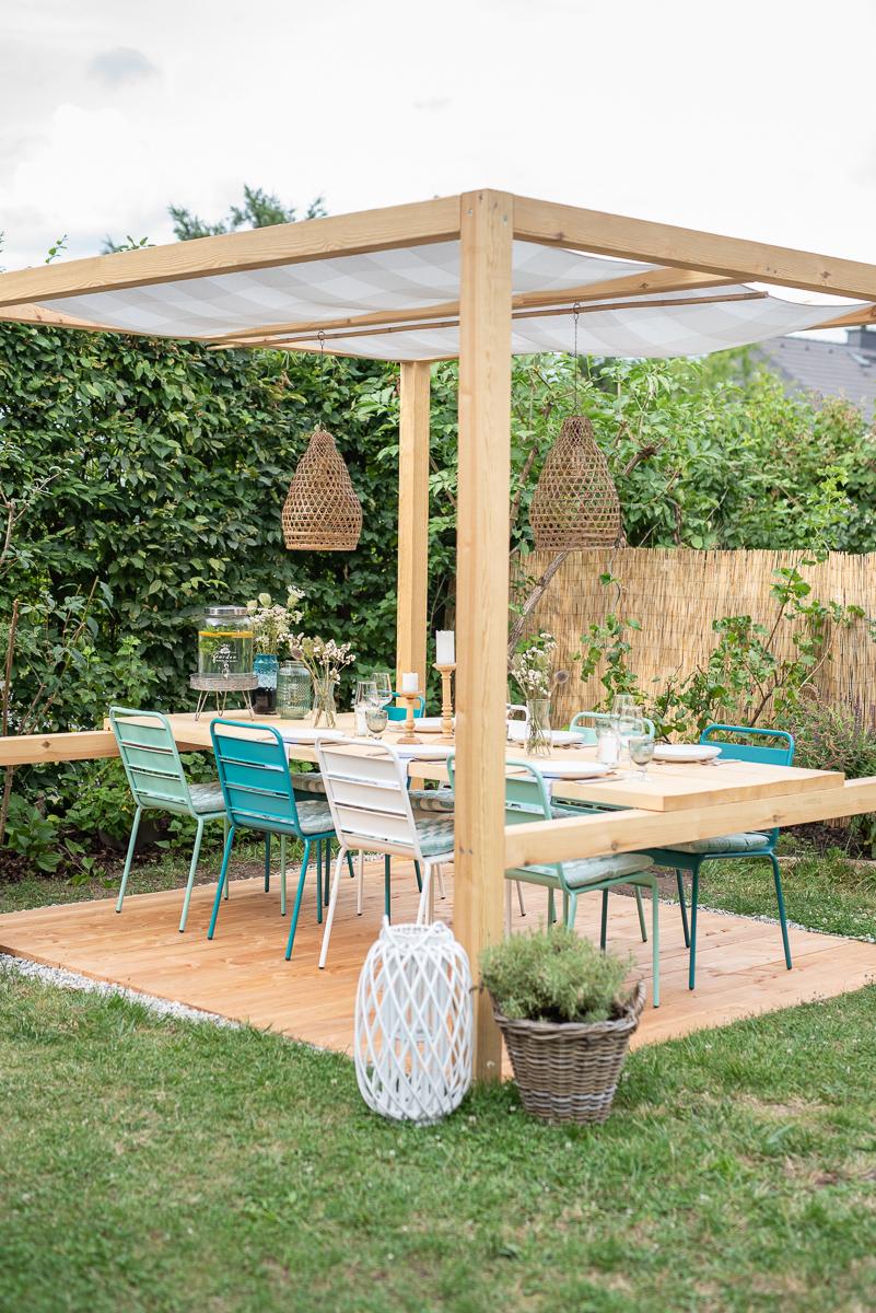 Selbst gebauter überdachter DIY Sitzplatz im Garten mit Tisch und Metallstühlen im Ibiza Look