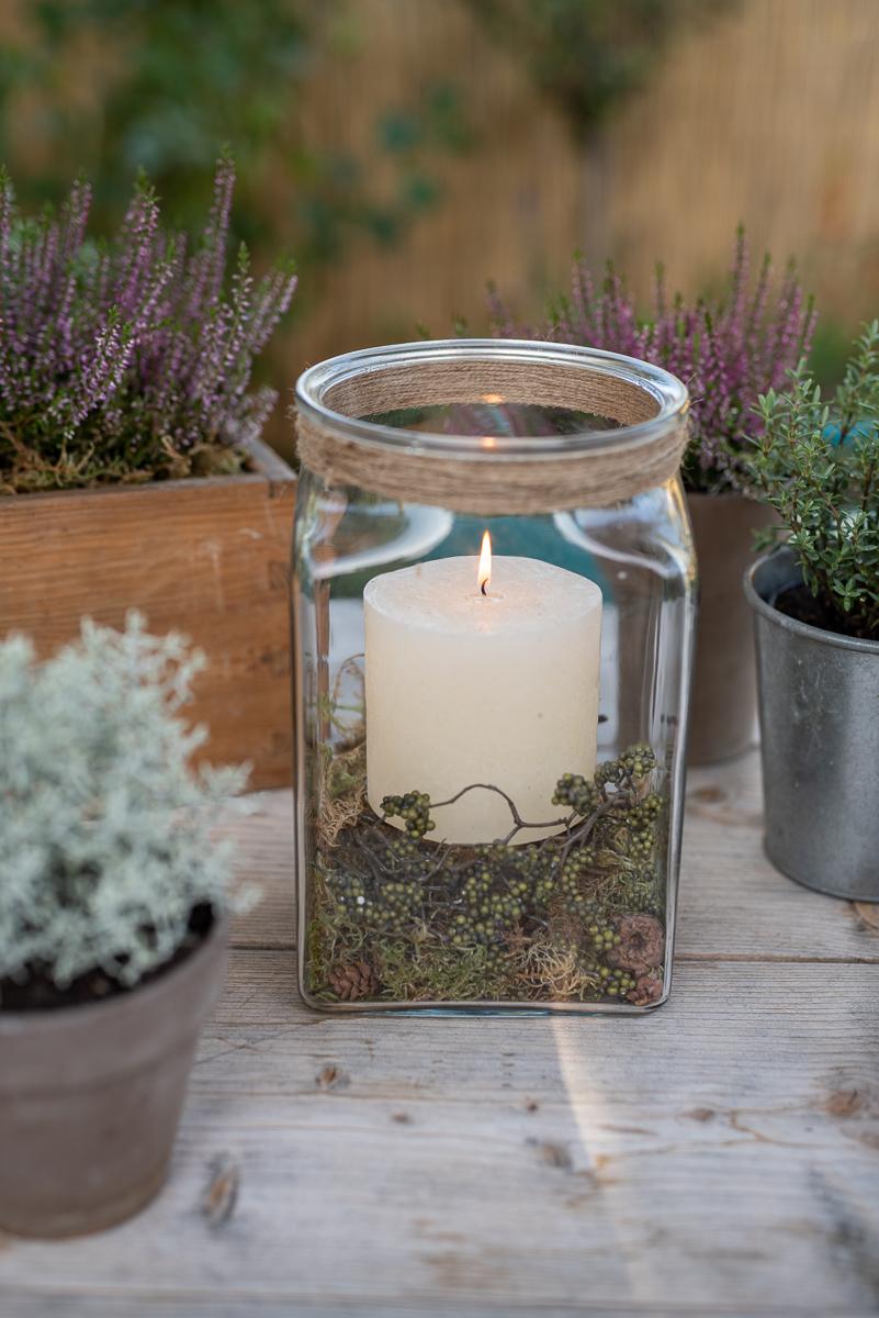Ideen für selbstgemachte DIY Deko für den Garten im Herbst mit Pflanzen wie Erika, Girlande aus Naturmaterial und Windlichtern mit Tannenzapfen als Herbstdeko auf dem Gartentisch