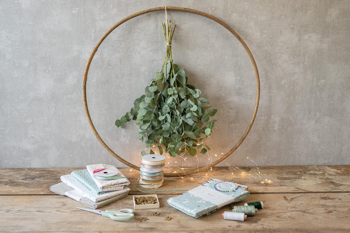 DIY Anleitung für einen selbst genähten, wiederverwendbaren Adventskalender mit Stoffbeuteln am Holzring mit Eukalyptus und Lichterkette
