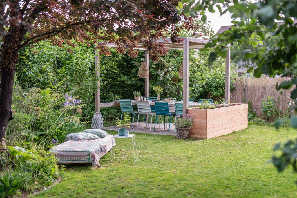 Selbst gebauter Sitzplatz im Garten mit Überdachung und Deko in Grüntönen für den Garten im natürlichen Boho Look