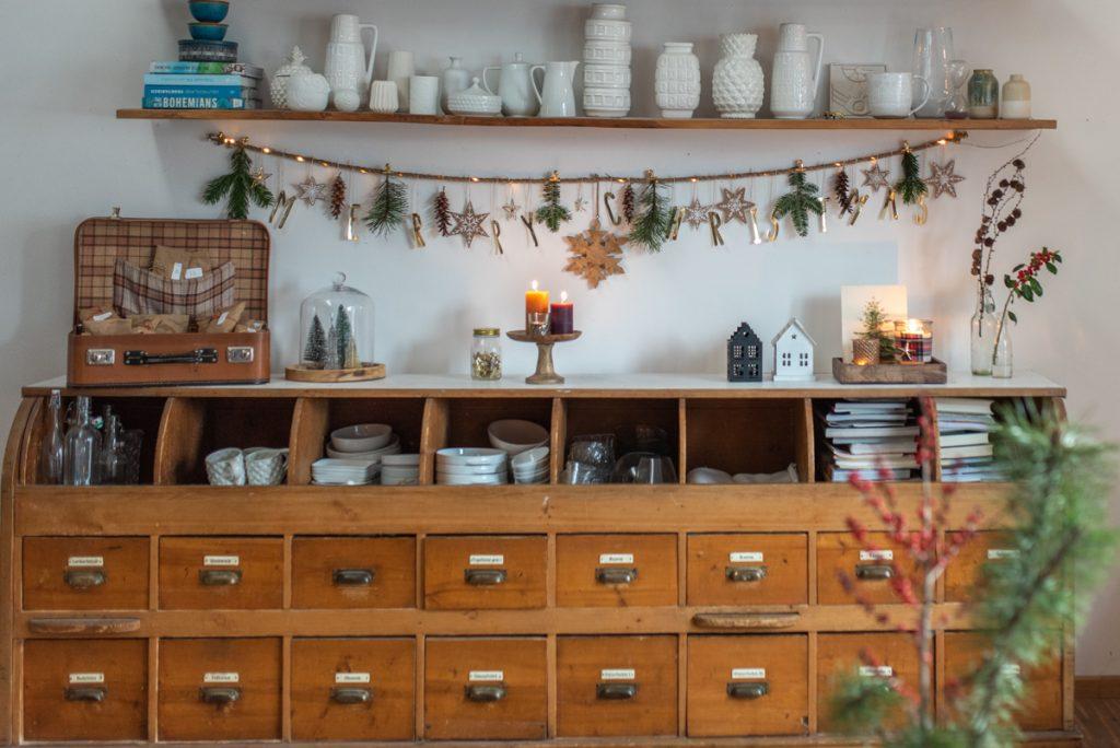Schnelle DIY Dekoideen für das Wohnzimmer zu Weihnachten im rustikalen Boho Farmhouse Look mit einer Girlande, DIY Sternen aus Kraftkarton und Windlichtern mit Karostoff