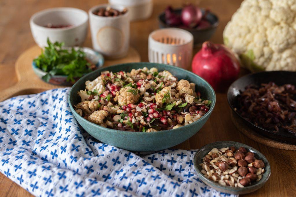 Rezept für lauwarmen Blumenkohlsalat mit karamellisierten Zwiebeln, Granatapfel und Zimt als vegane Vitamin Bowl für den Herbst